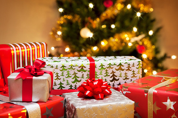 Group of Christmas gifts in front of tree.