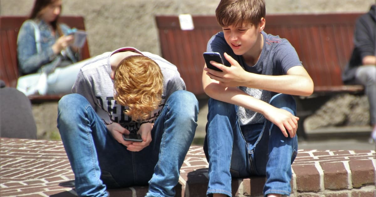 https://www.pexels.com/photo/2-boy-sitting-on-brown-floor-while-using-their-smartphone-near-woman-siiting-on-bench-using-smartphone-during-daytime-159395/